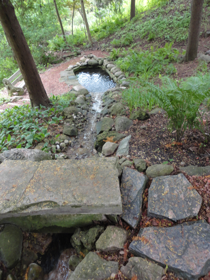 Step across this big flat rock across the hillside spillway which filters into the pond below...